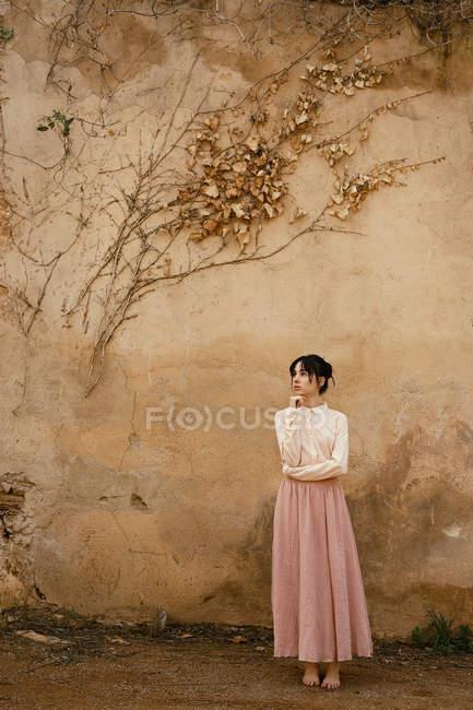 Задумчивая женщина позирует с подбородком на руке у стены с сухой листвы — стоковое фото