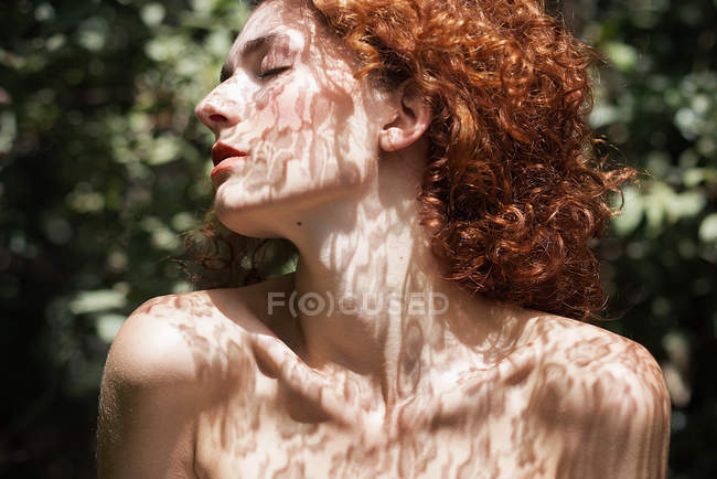Redhead woman standing sensually in shadows of lace with eyes closed — Stock Photo