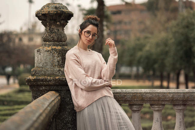 Pensive woman in glasses posing by stone handrail on terrace — Stock Photo