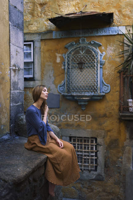 Side view of young calm woman sitting on  ledge and touching hair. — Stock Photo