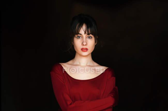 Bruna donna in abito rosso in posa contro il nero — Foto stock