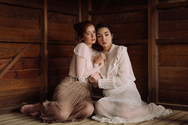 Tender brunettes wearing old-fashioned elegant clothes and embracing at wooden cabin — Stock Photo
