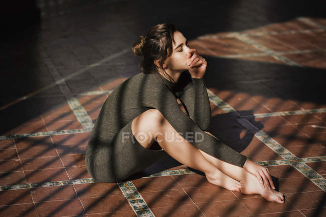 Sensual girl sitting on floor in sun rays with chin on hand — Stock Photo