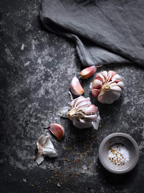 Still life of garlic and salt on stone surface — Stock Photo