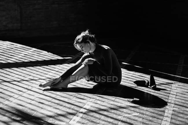 Чуттєвий дівчина сидить на підлозі в сонячних променів і зворушливо ніг — стокове фото