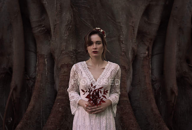 Young brunette woman in white lace dress and flowers in hair holding dark red foliage — Stock Photo