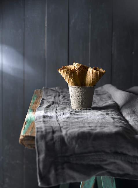 Склад вафельних ріжків в кухоль на сільському стилі таблиці — стокове фото