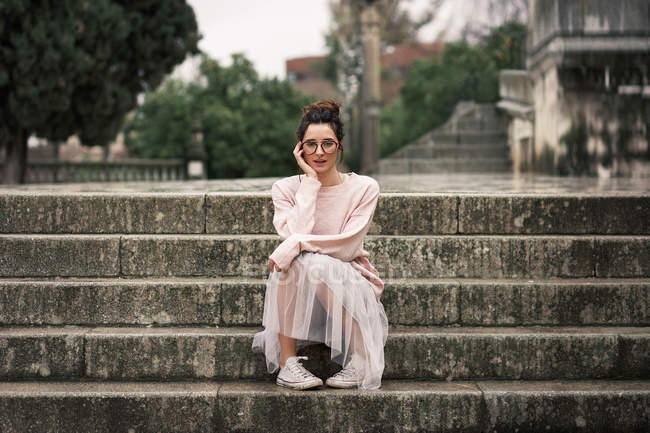 Stylish woman in skirt sitting on steps abd looking at camera — Stock Photo