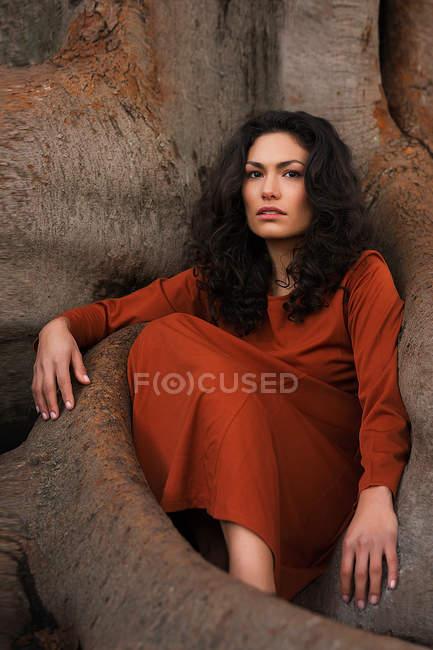 Bruna donna in abito rosso seduta tra grandi radici — Foto stock