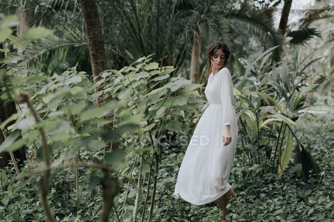 Fille romantique en posant blanc parmi les plantes tropicales avec des yeux fermés — Photo de stock