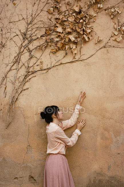 Side view of woman crawling hands on shabby wall with drying branches and leaves above. — Stock Photo