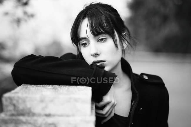 Чувственная брюнетка в черных пальто, опираясь на забор и задумчиво глядя — стоковое фото