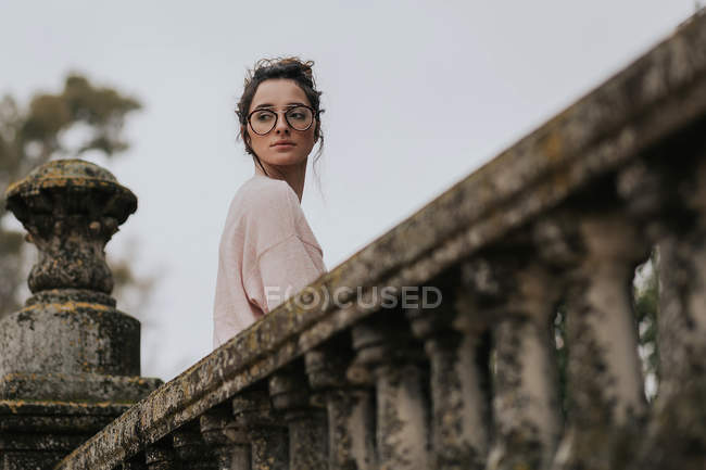 Pensive woman posing on terrace and looking over shoulder away — Stock Photo