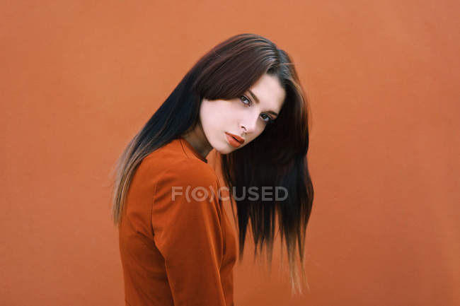 Portrait of brunette in brown looking at camera on brown backdrop — Stock Photo