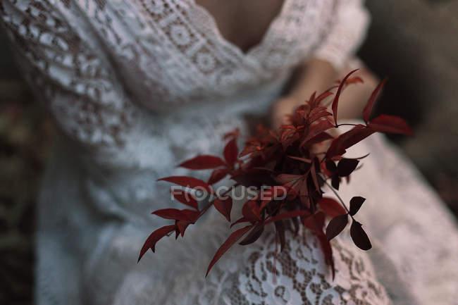 Средняя часть женщины в белом кружевном платье и с красной листвой . — стоковое фото