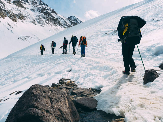 Rear view of people trekking  on snowy downhill — Stock Photo
