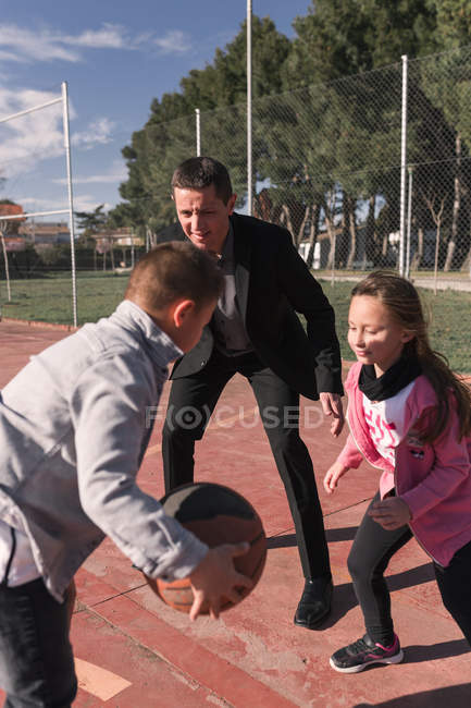 Father and children playing basketball — Stockfoto