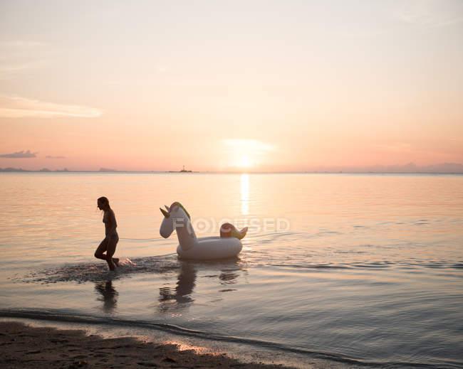 Женщина с игрушка надувные лошади в море — стоковое фото