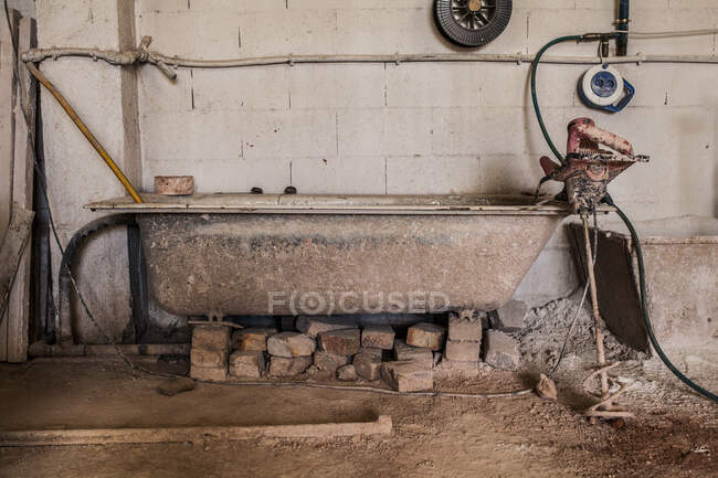 Side view of old dirty bath with cement standing on bricks and equipment in metal casting factory — Stock Photo
