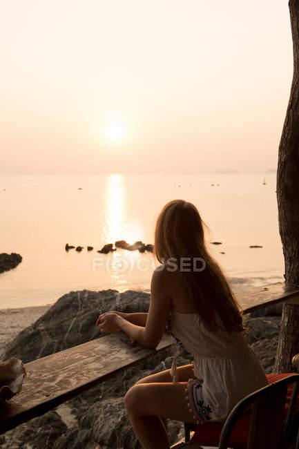 Woman looking at sunset on rocky beach — Stockfoto