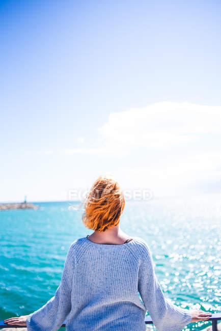 Donna in piedi al corrimano e guardando l'oceano — Foto stock