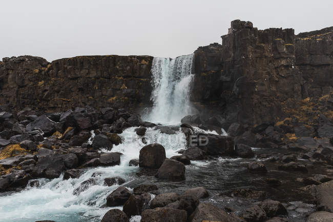 Water falling from rocky cliff — Stock Photo