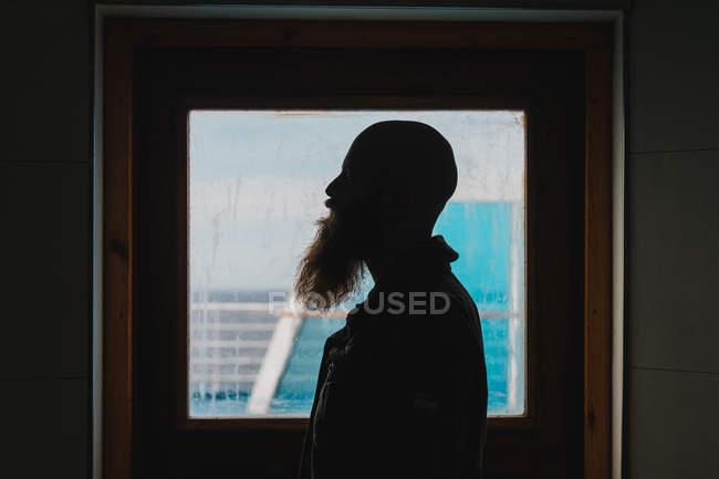 Человек, стоящий у окна на корабле — стоковое фото