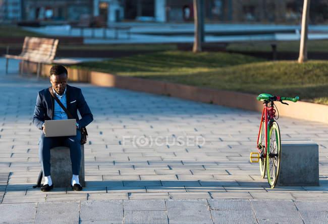Businessman sitting with laptop on street — Stock Photo