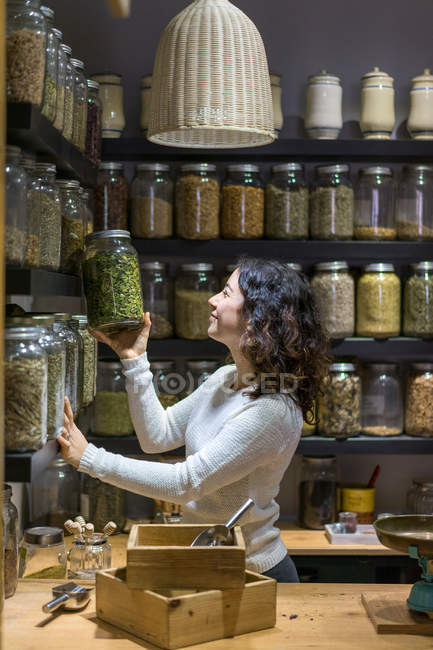 Woman taking jar with spice — Stock Photo