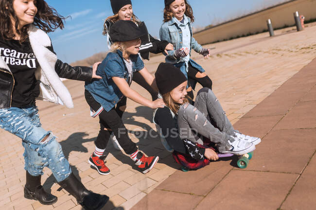 Group of trendy kids running and having fun while riding excited girl on skateboard in sunlight. — Stock Photo
