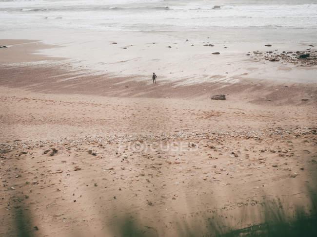 Touriste debout sur la plage de sable fin — Photo de stock