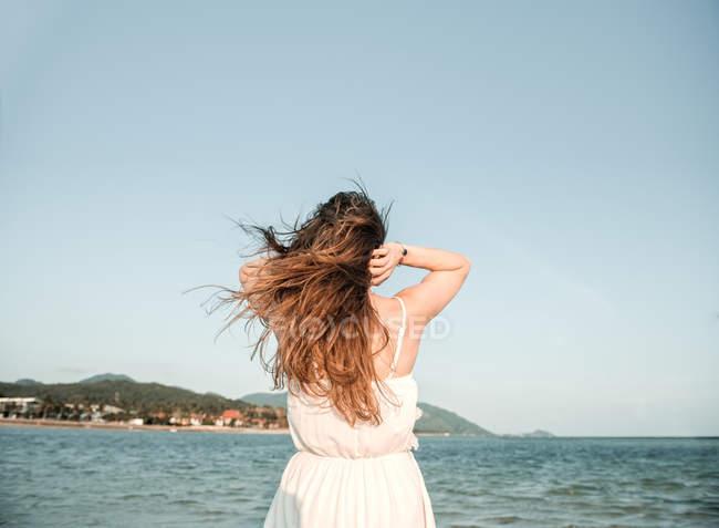 Femme cheveux au bord de mer de réglage — Photo de stock