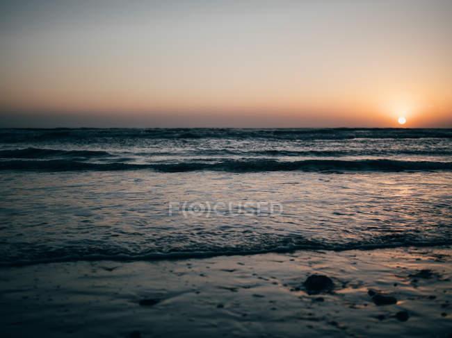 Ondulado oceano ao pôr do sol — Fotografia de Stock
