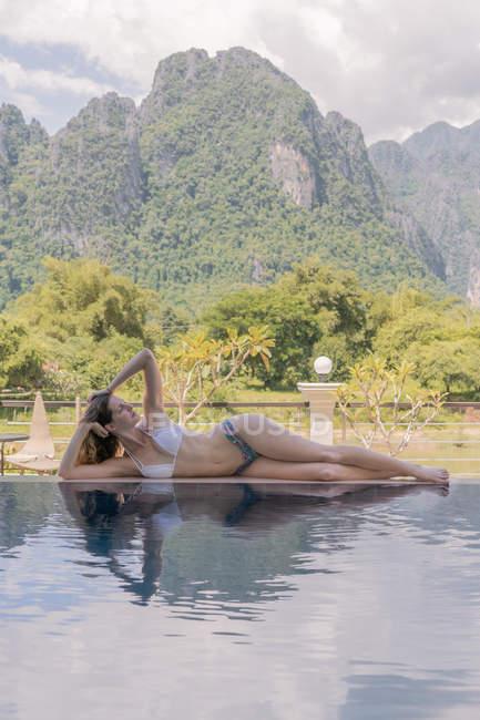 Женщина в бикини лежит у бассейна — стоковое фото