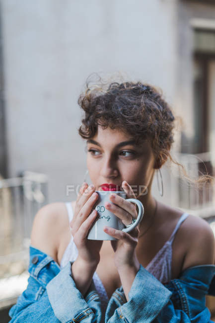 Curly woman with cup of coffee on balcony — Stock Photo