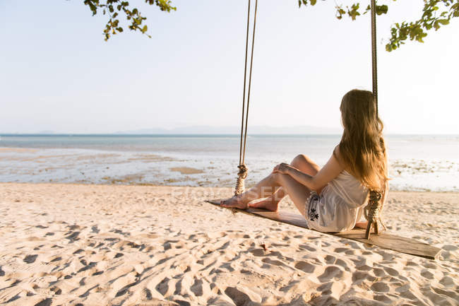 Woman sitting on swings on beach — Stock Photo