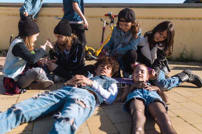 Group of rebel stylish kids chilling on street sidewalk relaxing and having fun in bright sunshine. — Stock Photo