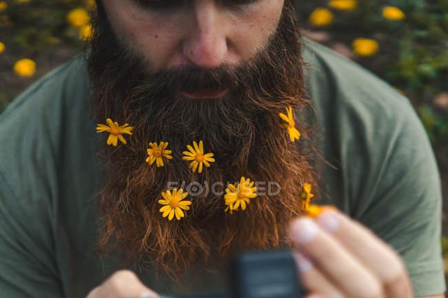 Человек с жёлтыми цветами в бороде — стоковое фото