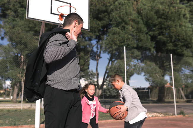 Father looking at children playing playing basketball — Stock Photo