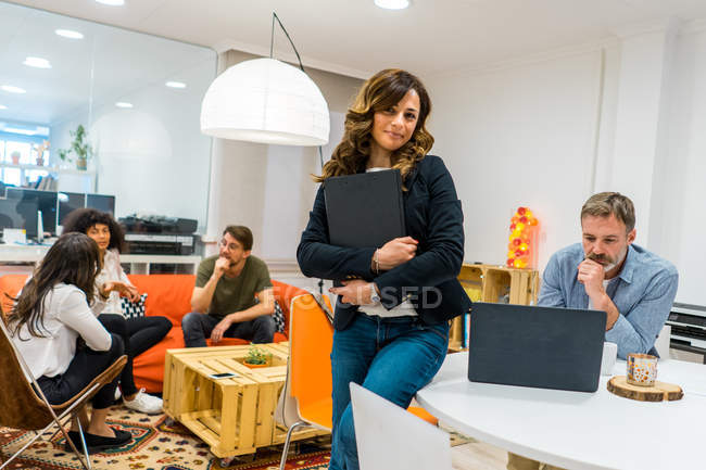 Businesswoman standing in creative office — Stock Photo