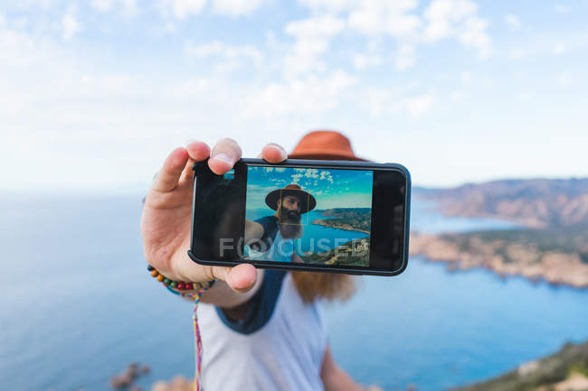 Uomo prendendo selfie sulla costa — Foto stock