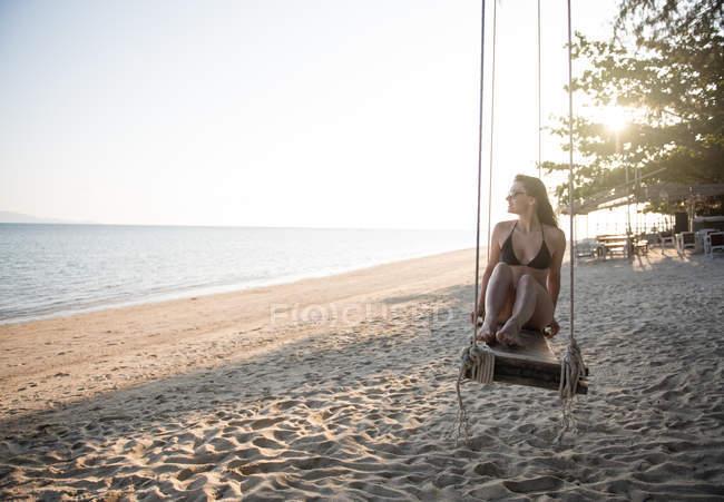 Жінка розслабляючий на гойдалки на пляжі — стокове фото