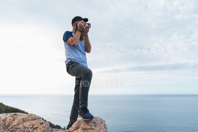 Uomo che scatta foto su roccia — Foto stock
