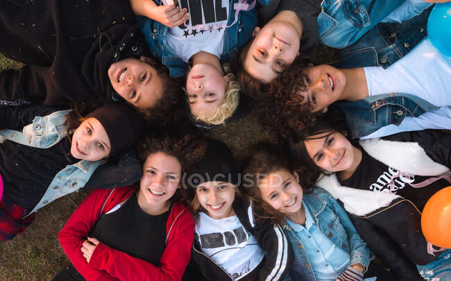 From above shot of cheerful teen kids in stylish clothes lying together in circle on ground laughing at camera. — Stock Photo