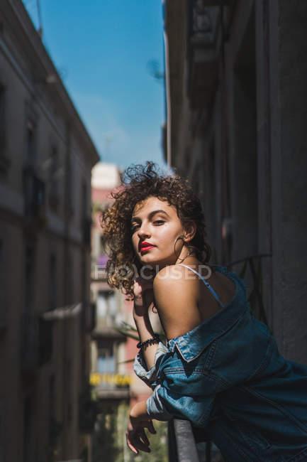 Woman standing on balcony in sunshine — Stock Photo