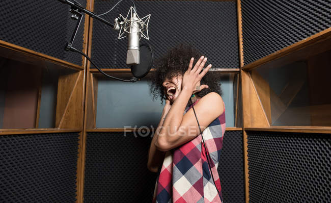 Woman singing in studio — Stock Photo