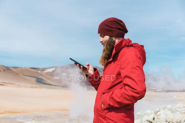 Mann mit Smartphone am Geysir — Stockfoto