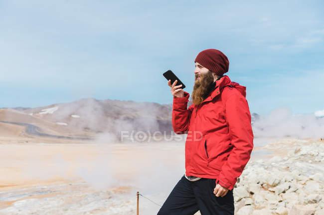 Mann benutzt Smartphone am Geysir — Stockfoto