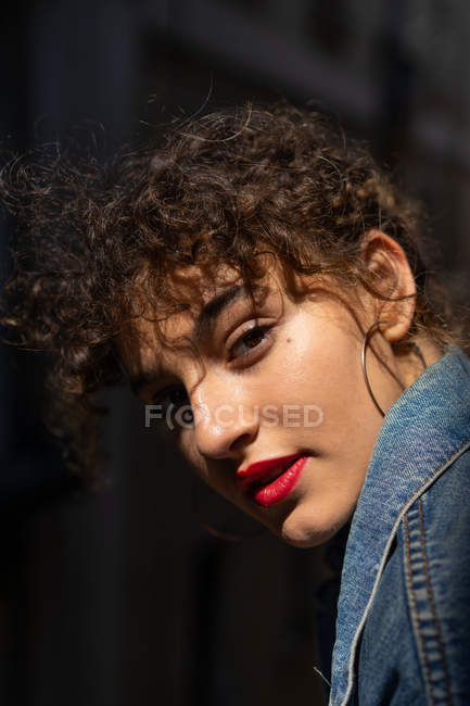 Curly young woman with red lips — Stock Photo
