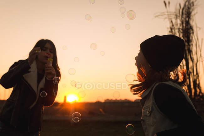 Kinder spielen mit Seifenblasen — Stockfoto